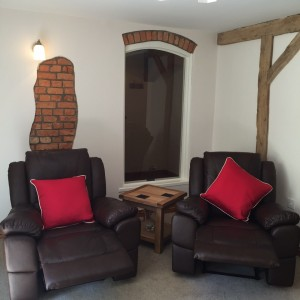 Leather Recliners Next To Open Brick Feature And Wooden Beam